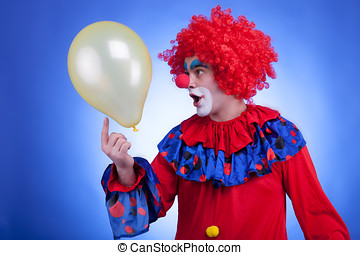 Happy clown with balloon on blue background