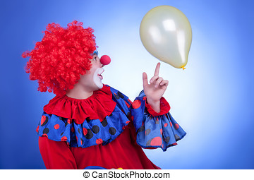 Happy clown playing with yellow ballon