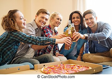 Group of young multi ethnic friends with pizza and bottles...