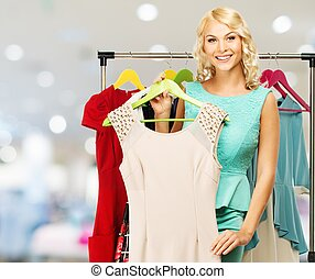 Smiling blond woman choosing clothes on a rack in a shopping...