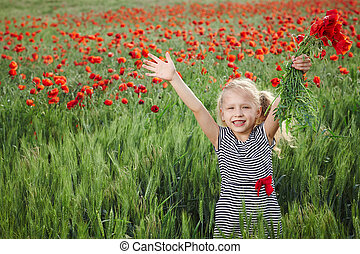 Little girl on the poppy meadow greeting happy with hands...