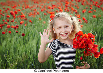 Little girl on the poppy meadow greeting waving her palm