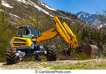 Yellow excavator working near mountains in summer