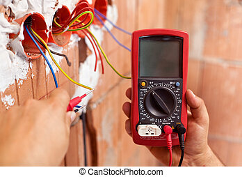 Electrician hands with multimeter and wires - Electrician...