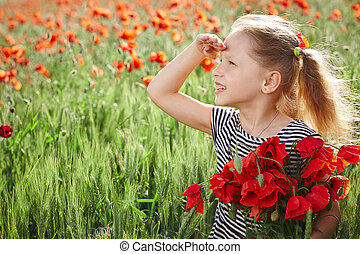 Little happy girl on the poppy meadow holding posy looking...