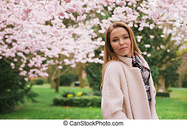 Beautiful young woman posing at spring garden