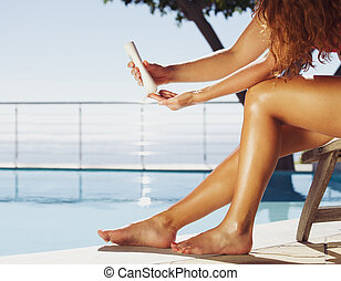 Women applying sun cream on legs - Woman sitting on deck...
