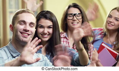 Salute - Group of teenagers cheerfully waving with the hand...