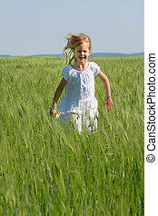 cute girl running in green grass