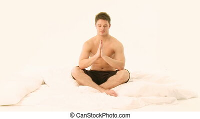 Young Handsome Man practicing Yoga on bed