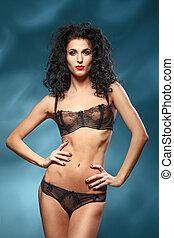 Portrait of sexy girl in underwear. Long black hair curls....