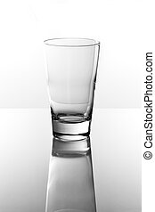 Empty drinking glass on a reflective tabletop