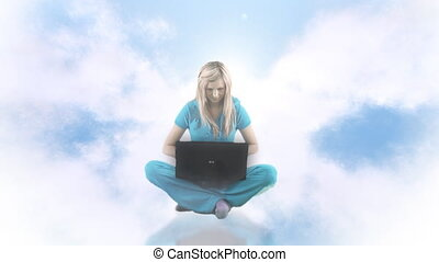 Woman up in clouds using laptop