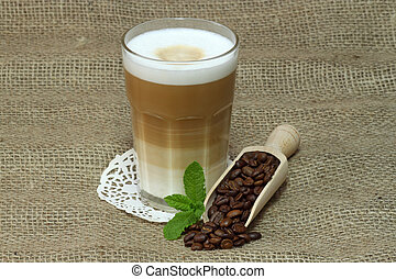 Latte Macchiato in glass with coffee grain on brown...