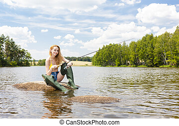 young woman fishing in pond during summer