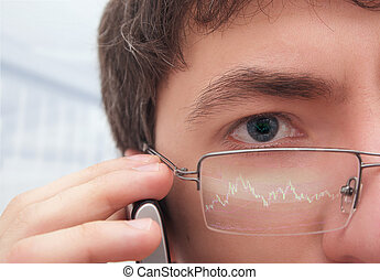 Financier in glasses looking at monitor.