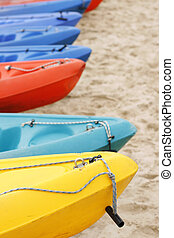 Colorful kayaks on the sand. - A row of colorful kayaks in...
