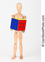 Happy wood mannequin hold cube puzzle confused after solving