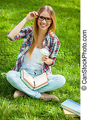 Happy student. Top view of beautiful young female student adjusting her glasses and smiling while sitting in a park with books around her