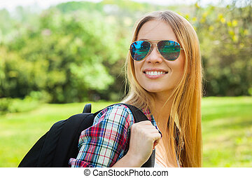 Beautiful hiker Beautiful young woman in sunglasses carrying...