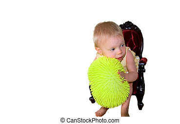 Toddler Holding Ball In Chair Bending Over - This cute 1...