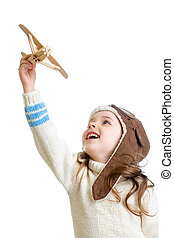 child girl dressed pilot helmet and playing with wooden airplane toy