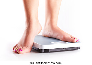 A pair of female feet on a bathroom scale - A pair of female...