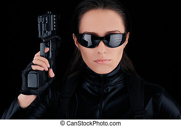 Woman Spy Holding Gun - Woman in a black leather suit...