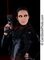 Woman Spy Holding Gun with Laser - Woman in a black leather...