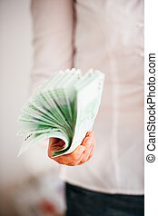 Money used as paper fan - Money stack used as paper fan by...
