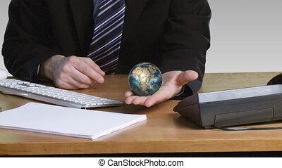 Businessman with a rotary terrestrial globe in his open hand