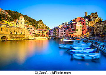 Vernazza village, church, boats and sea harbor on sunset,...