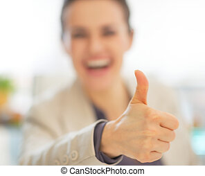 Closeup on happy business woman showing thumbs up