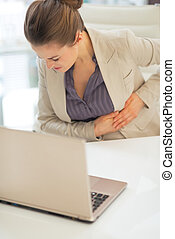 Portrait of business woman with stomach ache in office