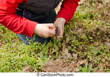 Young child lighting a match setting fire to a pile of dead...