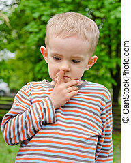 Little boy standing picking his nose - Candid image of a...