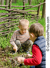 Two young boys discussing lighting a campfire with one...