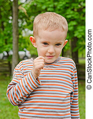 Cute young boy pulling a funny expression puckering up his...