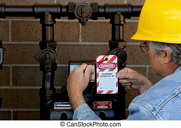 man attaching lockout tag to a meter