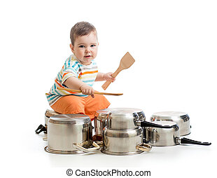 young boy using wooden spoons to bang pans drumset