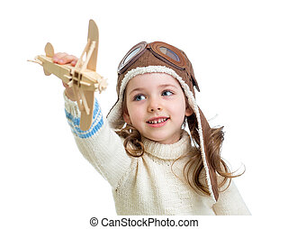 child dressed as pilot and playing with wooden airplane toy isolated on white background