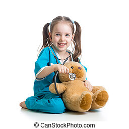 Adorable child with clothes of doctor examining teddy bear...