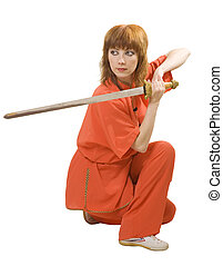 woman makes exercise with sword - young woman makes kung-fu...