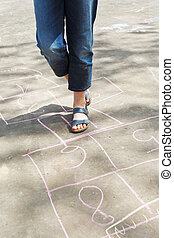girl hoping in hopscotch outdoors - girl hopping in...