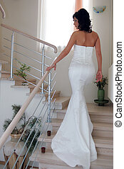 Bride walking up staircase - Rear view of young bride...