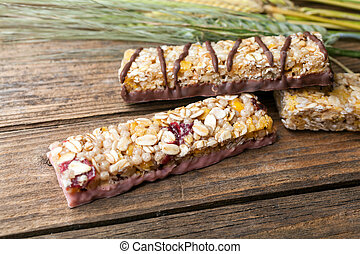 Cereal bars and dry wheat on a wooden table