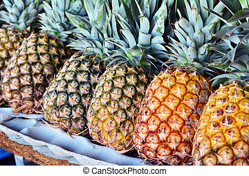 Pineapples on display in open market.