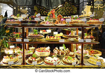 Pastry shop display window with variety of cakes