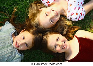 Three girls lying on grass