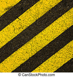 Yellow striped road markings on black asphalt. - Yellow...